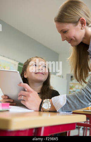 Female teacher showing a girl something on digital tablet pc in classroom, Munich, Bavaria, Germany - Stock Photo