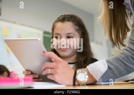 Female teacher showing a schoolgirl something on digital tablet pc in classroom, Munich, Bavaria, Germany - Stock Photo