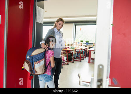 Female teacher welcoming student in classroom on first day of school, Munich, Bavaria, Germany - Stock Photo