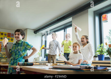 School children playing with paper airplanes in classroom, Munich, Bavaria, Germany - Stock Photo