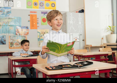 Schoolboy reading a book in classroom, Munich, Bavaria, Germany - Stock Photo