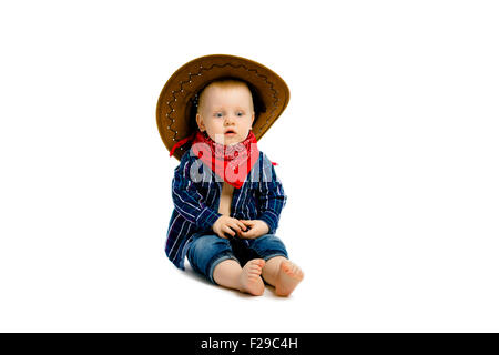 baby boy in a cowboy hat sitting on a white floor - Stock Photo