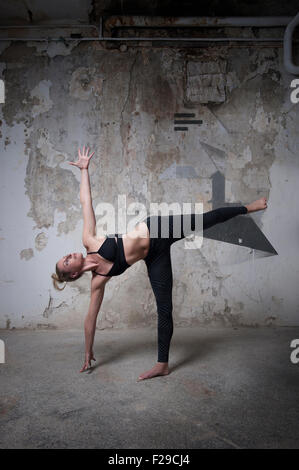 Mid adult woman practicing half moon pose in yoga studio, Munich, Bavaria, Germany - Stock Photo