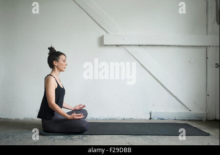 Side profile of a mid adult woman practicing lotus pose in yoga studio, Munich, Bavaria, Germany - Stock Photo