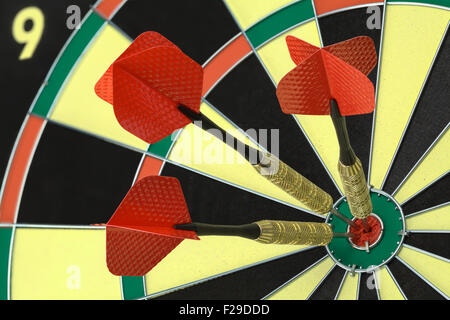Three Darts in the Bulls Eye on Dart Board. - Stock Photo