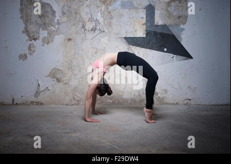 Mid adult woman practicing bridge pose in yoga studio, Munich, Bavaria, Germany - Stock Photo