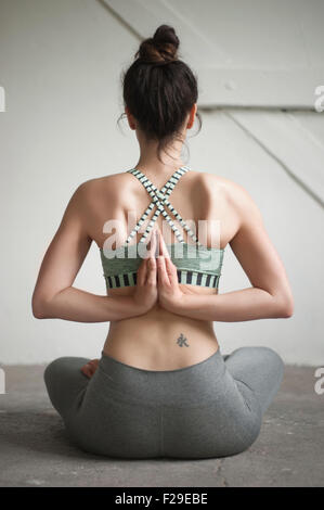 Rear view of a mid adult woman doing pashchima namaskarasana position in yoga studio, Munich, Bavaria, Germany - Stock Photo