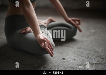 Woman practicing lotus pose in yoga studio, Munich, Bavaria, Germany - Stock Photo
