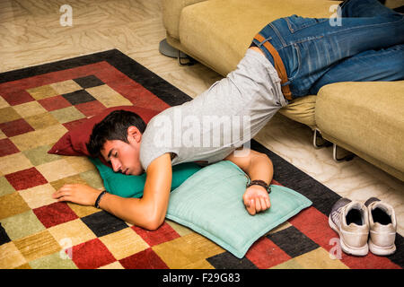 Drunk Young Handsome Man Resting on Couch in the Living Room with Head on the Floor. - Stock Photo