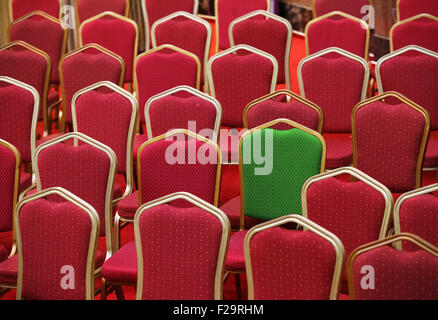 Diversity, different or unique concept - green chair in a group of red ones - Stock Photo
