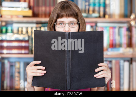 girl with glasses reads big book with blank cover and book shelves on background - Stock Photo