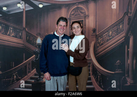 young couple pose in front of titanic grand staircase backdrop on board a cruise ship - Stock Photo