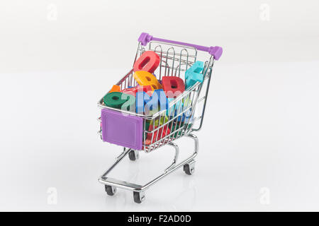 Toy shopping cart filled with letters and numbers - back to school concept isolated on white - Stock Photo