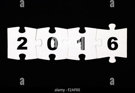 Four pieces of puzzle with numbers 2016 are connected together on black background - Stock Photo