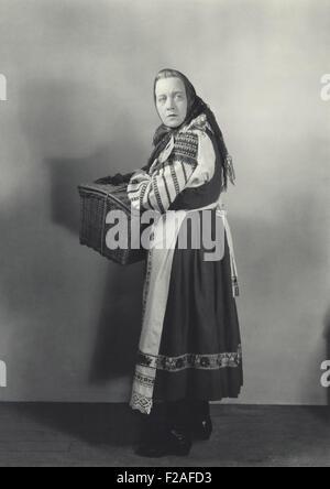 Woman in peasant dress carrying basket (OLVI008_OU467_F) - Stock Photo
