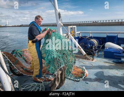 Fisherman preparing fishing net on research ship - Stock Photo