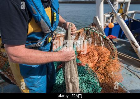 Fisherman preparing fishing net on research ship, close up - Stock Photo