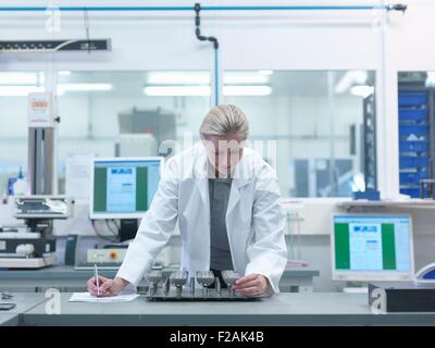 Female engineer inspecting artificial hip joint parts in quality control department in orthopaedic factory - Stock Photo