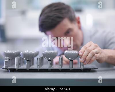 Engineer inspecting artificial hip joint parts in quality control department in orthopaedic factory - Stock Photo