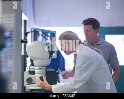 Engineers inspecting artificial hip joint parts using electron microscope in orthopaedic factory - Stock Photo