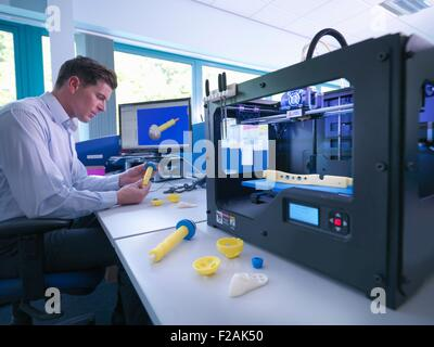 Medical product designer with 3D printing machine with CAD design on screen in orthopaedic factory - Stock Photo