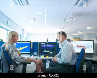 Medical product designers with 3D printing machine with CAD design on screen in orthopaedic factory - Stock Photo