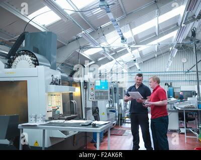 Engineers discussing work in front of CNC machines in engineering factory - Stock Photo
