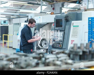 Male worker inspecting parts on CNC lathe in engineering factory - Stock Photo