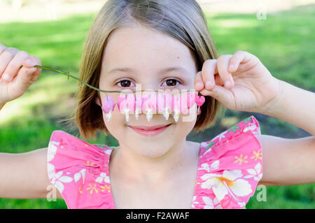 Little girl holding bleeding heart plant stem - Stock Photo