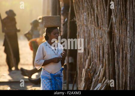 Malagasy woman carrying basket on her head in the town Bekopaka, Antsalova, Melaky, Madagascar, Southeast Africa - Stock Photo