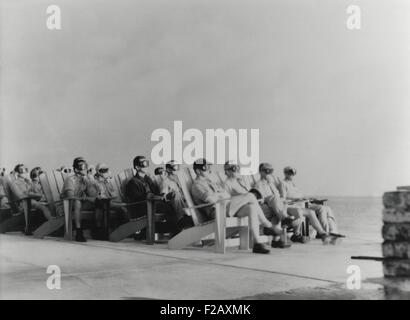 VIPs view the DOG shot, an 81 kiloton atomic detonation wearing safety goggles. They are sitting on Adirondack chair - Stock Photo