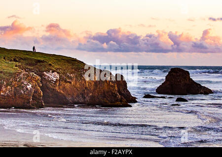 Three people enjoy the sunset in Fort Bragg California where Pudding Creek flows into the Pacific ocean - Stock Photo