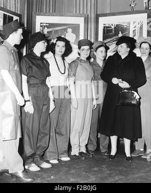 Secretary of Labor Frances Perkins examines work clothes for women. March 1, 1943. The work clothes for women were - Stock Photo