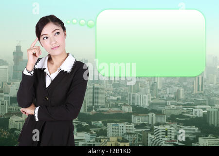 Thinking business woman with many ideas in empty bubble with city background - Stock Photo