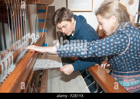 Two young women weave linen on a traditional hand loom. - Stock Photo