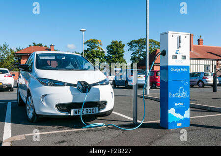 A Renault Zoe electric car is recharged from a Northern Ireland Electricity charging station in a car park - Stock Photo