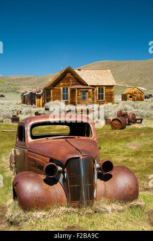 Log cabins and an abandoned decaying car  at Bodie State Historic Park  a Californian gold-mining ghost town. - Stock Photo