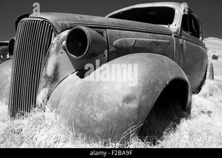 Shell of large rusting American car on rough ground in historic Bodie Park, California. - Stock Photo