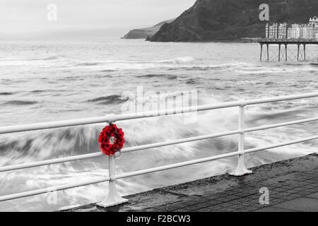 Poppy Wreath hanging on seaside railings on remembrance day UK - Stock Photo