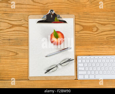 Top view of clipboard, computer keyboard, reading glasses, apple, paper and pen on desktop. - Stock Photo