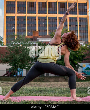 Attractive young woman practicing yoga in the park (Extended Side Angle) - Stock Photo