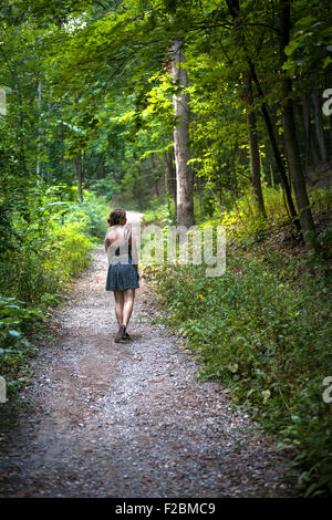 Contemplative young woman wearing summer dress standing on path in green dense forest - Stock Photo