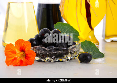 Salad Dressing with oils, olives and vinegars on white wood table, closeup on olives. - Stock Photo
