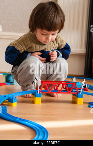 Caucasian child, boy, 3 - 5 year old, at home in room with wooden floor, crouching down looking at Tommy Tank engine - Stock Photo