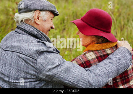 Back view of affectionate seniors interacting in natural environment - Stock Photo