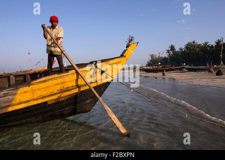 Local fisherman, standing on the bow of a fishing boat on the beach of the fishing village Ngapali, fishing boats - Stock Photo