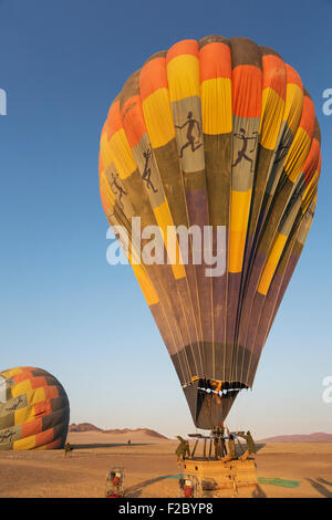 Pilot inflating hot air balloon with two burners, preparing for take-off at sunrise, second balloon behind, Namib - Stock Photo