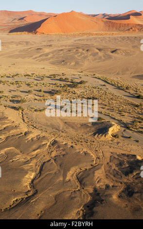 Arid plains and dry riverbed of the Tsauchab river at the edge of the Namib Desert, paved road connecting Sesriem - Stock Photo