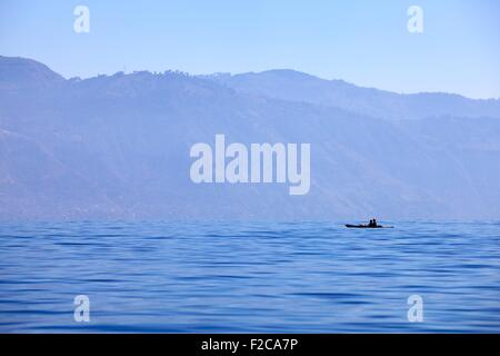 Deep blue: Lake Atitlan a small boat in silhouette against Tuliman volcano - Stock Photo
