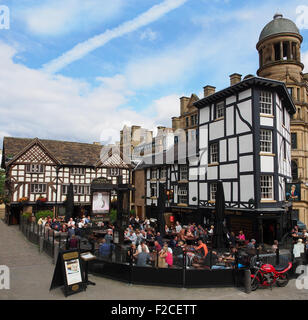 people in the crowded seating area outside the Old Wellington Inn and Sinclairs Oyster Bar in the city centre, Manchester, - Stock Photo